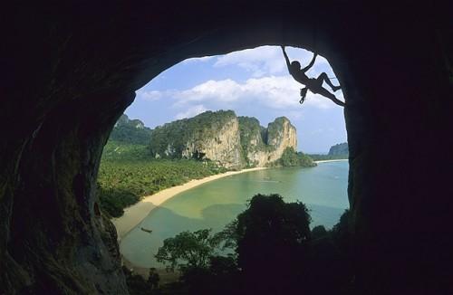 Silueta de una mujer escalando en la cueva de la playa de Ton Sai, Tailandia.