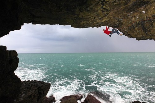 Un escalador trepa por una cueva en el mar cerca de Swanage, Dorset.