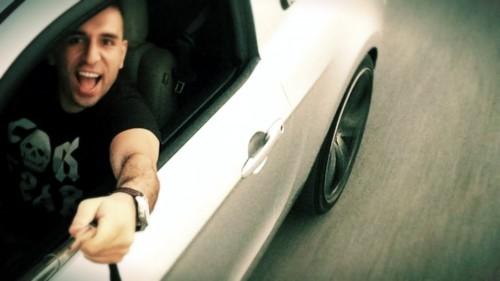 un conductor sacando el palo afuera del auto poara tomarse una selfie